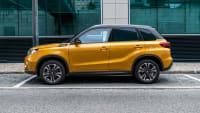 goldener Suzuki Vitara steht vor Gebauede