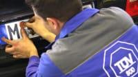 Mechaniker klebt TÜV Plakette aufs Kennzeichen