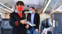 Schaffnerin mit Munschutz scannt kontaktlos das Ticket einer Zugreisenden im Fernverkehr der deutschen Bahn