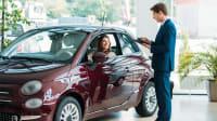 Eine frau b eim Autokauf in einem Autohaus