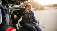 Mann sitzt mit seinem Hund im Kofferraum