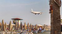 Eine Maschine der Aegean Airline fliegt über Badegäste am Mc Kenzie Beach in Zypern