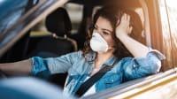 Eine Frau mit Maske sitzt angeschnallt in einem Auto