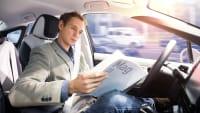 Mann liest Zeitung im autonomen Fahren