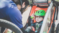 Vater kümmert sich um Sohn im Fahrradanhänger
