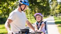 Vater kommuniziert mit Tochter im Fahrradsitz