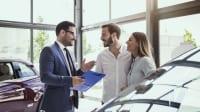 Ehepaar wird im Autohaus von Verkäufer beraten