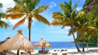 Karibischer Strand mit Palmen und Sonnenschirmen aus Palmblättern