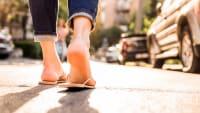 Eine Frau läuft mit Flip Flops über eine Strasse