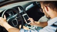 Mann nutzt Handy während der Autofahrt