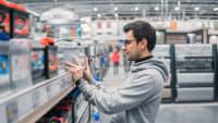 Mann kauft eine Autobatterie