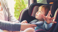 Kleinkind wird von Frau im Kindersitz angeschnallt