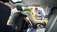 Baby wird von Frau in einen Kindersitz im Auto gesetzt