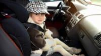 Kleinkind sitzt auf einem Kindersitz am Beifahrersitz in Fahrtrichtung
