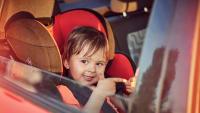 Kleiner Junge sitzt in Kindersitz auf der Rückbank