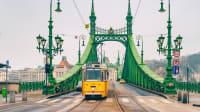Eine Strassenbahn fährt über eine Brücke in Budapest.