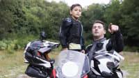 Vater und Kind stehen beim Motorrad