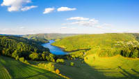 Weiter Blick über eine hügelige Landschaft mit See