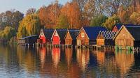 Bootshäuser an einem See im Herbst