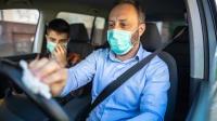 Autofahrer trägt Mundschutz und reinigt Lenkrad