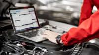 Mechaniker wertet Daten eines Autos mit Laptop aus