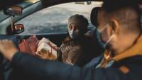 Mann und Frauen fahren mit Weihnachtsgeschenken Auto