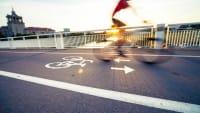 Ein Pedelec-Fahrer fährt schnell über eine Brücke