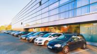 Autos auf einem Mitarbeiterparkplatz vor einem Bürogebäude