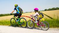 Kinderfahrrad eines Mädchen ist mit einer Tandemstange am Fahrrad des Vaters befestigt