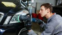 Junger Mechaniker poliert einen Autoscheinwerfer