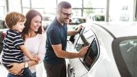 junge Familie begutachtet ein neues Auto beim Händler