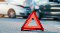 Ein Warndreieck steht auf der Straße, im Hintergrund ein Unfall.