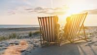 zwei leere Liebestühle am Strand bei Sonnenuntergang