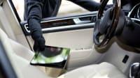 Schwarzgekleideter Dieb klaut Tablet durch ein Autofenster