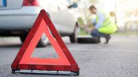 Warndreieck steht auf der Straße vor einem Auto mit einer Panne