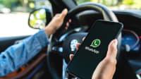 Frau nutzt die App WhatsApp während der Autofahrt