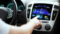 Ein Autofahrer bedient den Touchscreen eines Autos