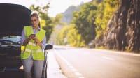 Frau mit Autopanne schaut in Handy