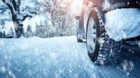 Vereiste Winterreifen an einem Auto früh morgens auf einer verschneiten Straße im Winter