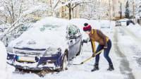 Frau schaufelt eingeschneites Auto frei