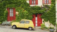 Gelber Renault R4 parkt vor einem weinbehangenen Haus in Frankreich