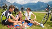 Familie picknickt während einer Radtour auf einer Wiese