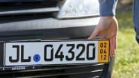 Ein Mann befestigt an einer Prägestelle in Bad Oldesloe ein Kurzzeitkennzeichen an einem Auto.