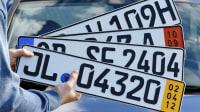 Ein Mann hält ein H-Kennzeichen für historische Fahrzeuge (v. oben), ein Ausfuhrkennzeichen, ein Euro-Kennzeichen und ein Kurzzeitkennzeichen vor ein Auto.