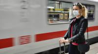Frau steht mit Mundschutz zur Corona-Zeit am Bahnsteig vor Zug der Deutschen Bahn