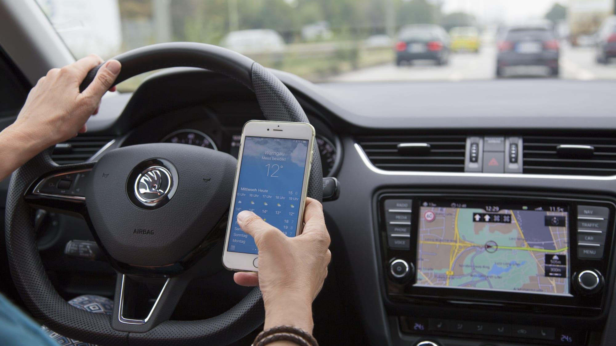 Mann schaut während des Autofahrens auf sein Handy