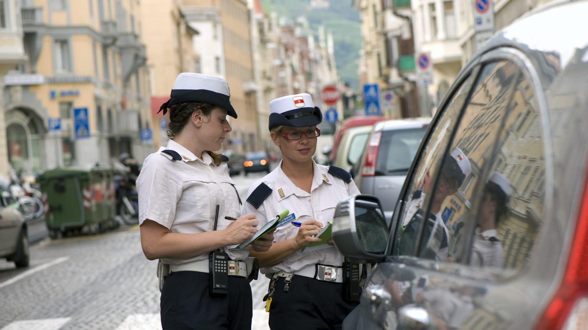 Zwei italienische Politessen schreiben in Bozen einen Strafzettel für ein parkendes Auto