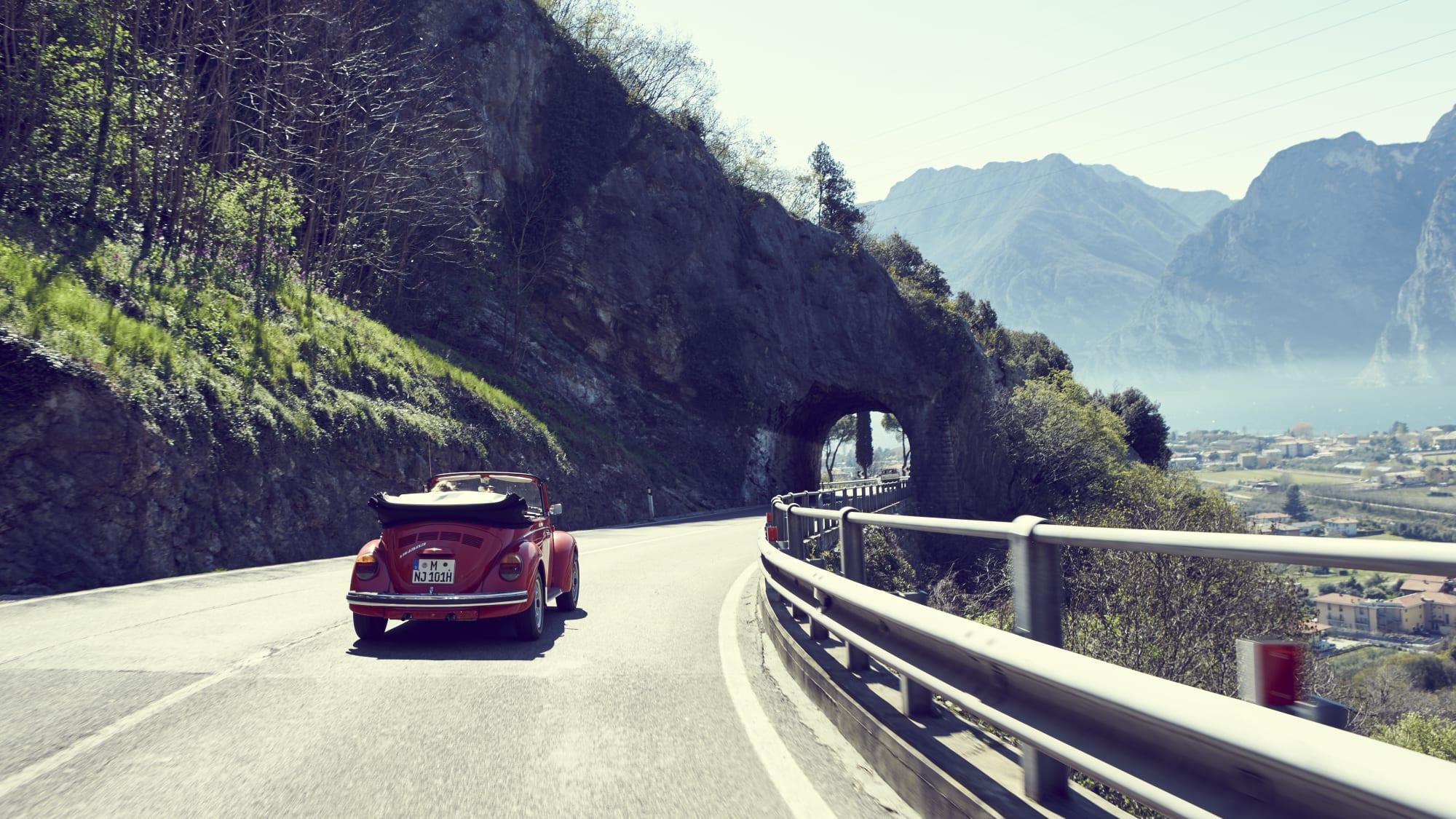 Rotes Oldtimer VW Käfer Cabriolet faährt auf der Panoramastraße Richtung Torbole