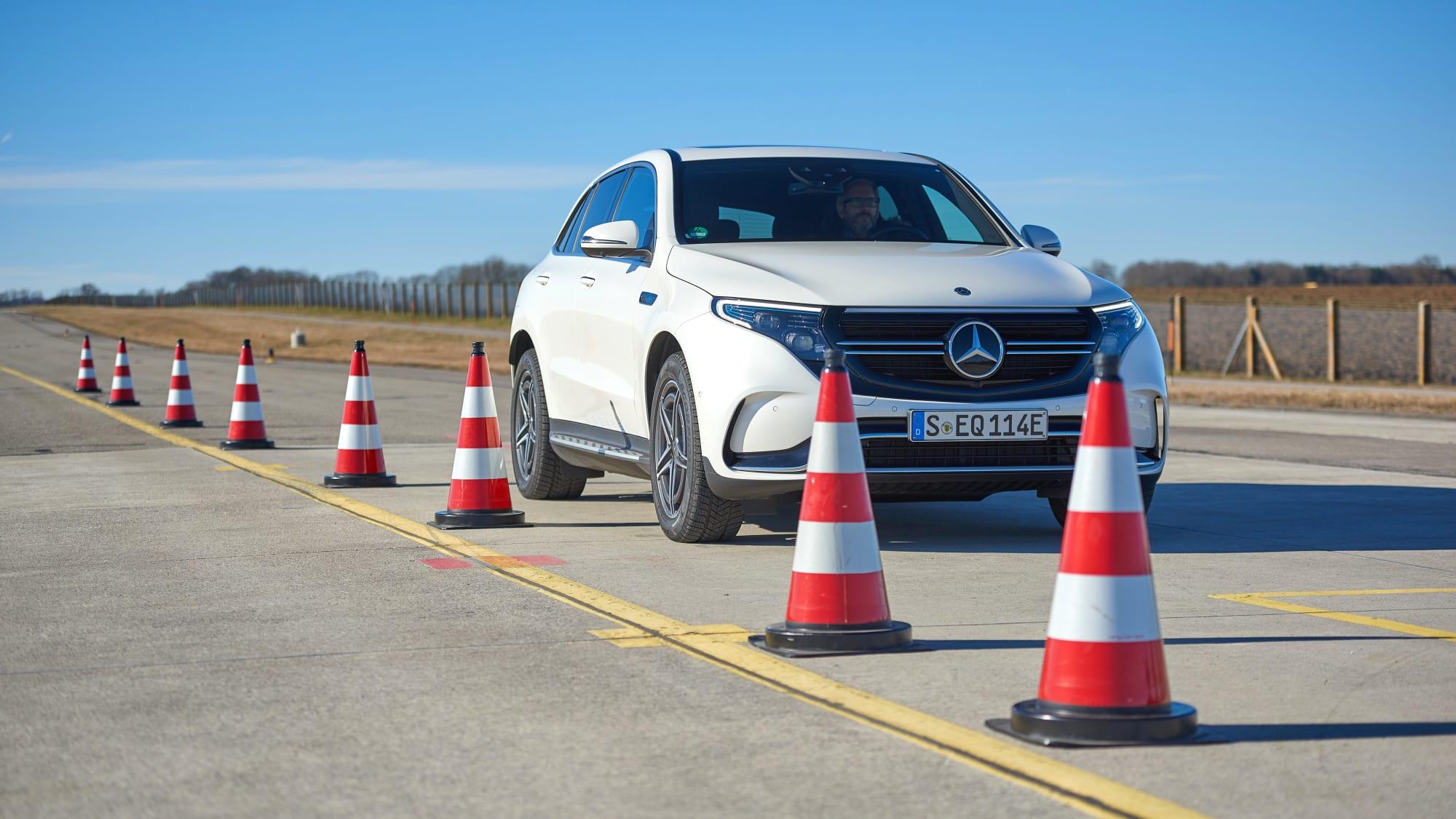 Mercedes EQC fährt neben Pylonen