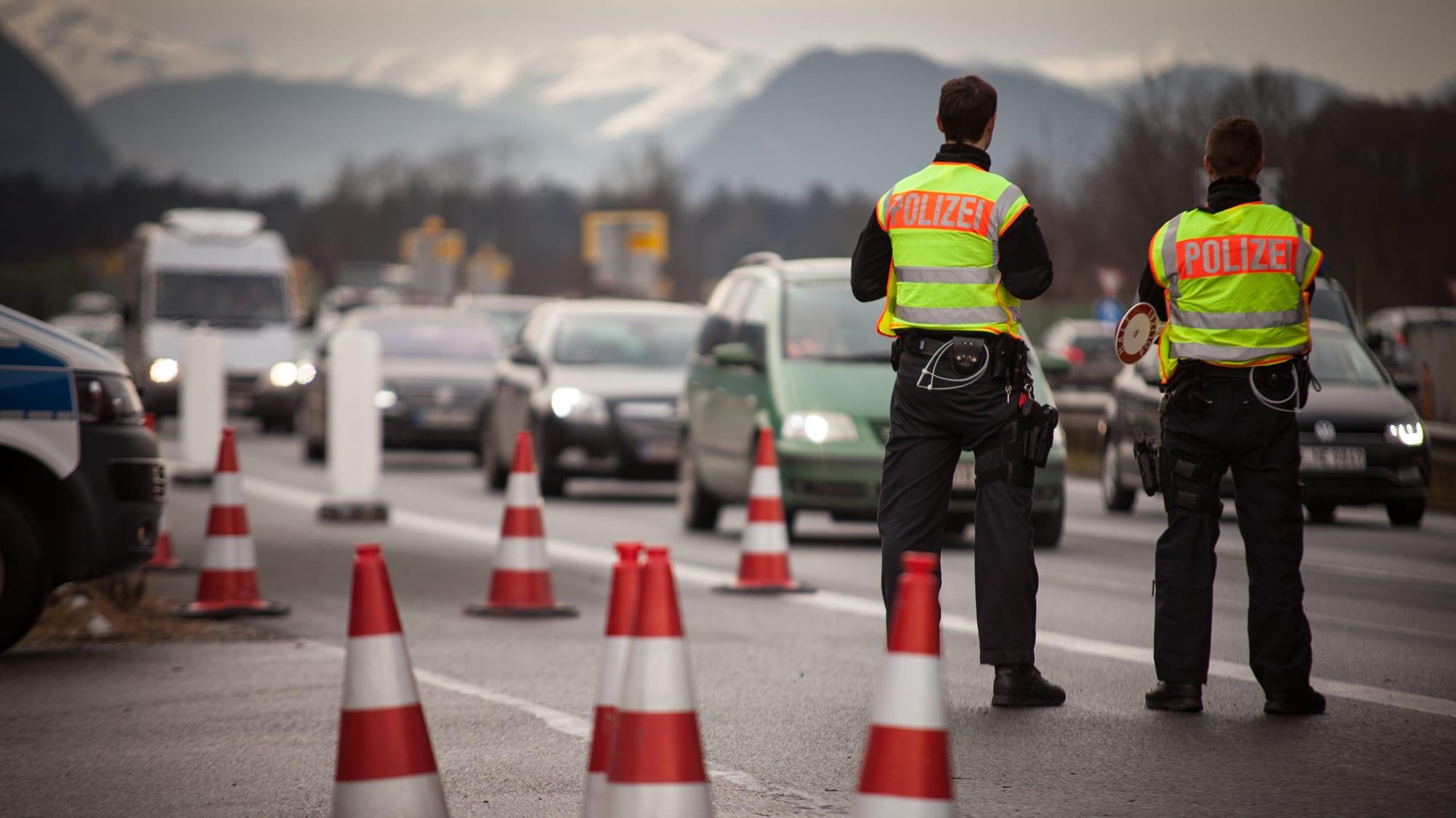 Zwei Polizisten stehen auf der Autobahn und kontrollieren an der Grenze von Deutschland zu Österreich.